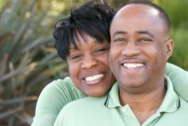 African American couple smiling and hugging.
