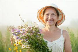 Smiling middle aged woman in a straw hat holding bouquet of wildflowers