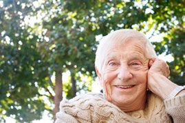 Elderly Caucasian man smiling with hand to his cheek cradling his face