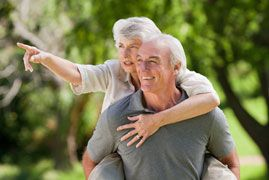 Happy looking elderly couple with woman riding piggyback and pointing in distance
