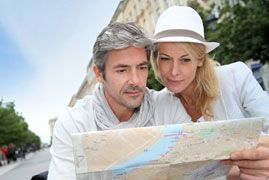 Middle aged couple reading a map on vacation