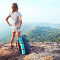 Woman at top of mountain with backpack, looking out at picturesque valley