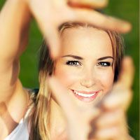 Pretty young blond making frame out of hands in front of face