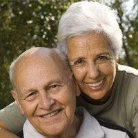Happy looking elderly couple smiling and hugging