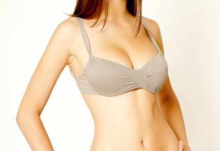 A woman's chest can be seen in a beige bra