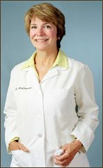Dr. Marilyn Mehlmauer with her short, light brown hair is wearing a white lab coat with her hands in her pockets, smiling.