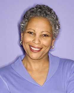 African-american woman smiling against purple wall
