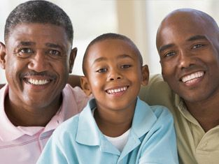 Three generations of black men with beautiful smiles put their arms around one another.