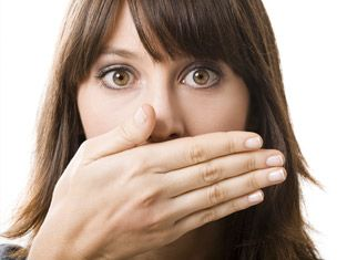 Brunette woman with bangs looks surprised while covering her mouth with her hand.