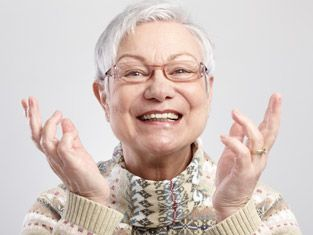 Senior citizen Caucasian woman wears chunky sweater and short, white hair.