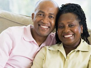 African-American middle-aged couple sits on couch smiling, beautiful teeth