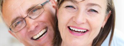 A middle-aged couple smiles with dental implants