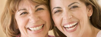A mother and daughter smile after receiving porcelain veneers