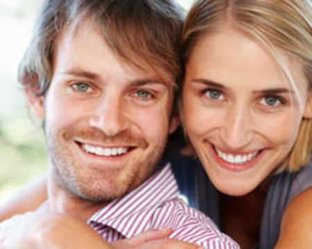 A young couple smiles together after their smile makeovers