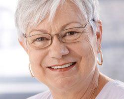 An older woman smiles after having dental bridges placed