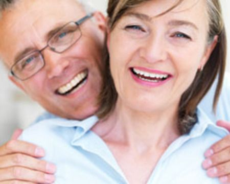 A couple smiles joyfully after having their dental implants restored