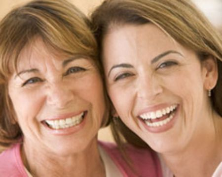 Two women smile joyfully after their porcelain veneers treatment