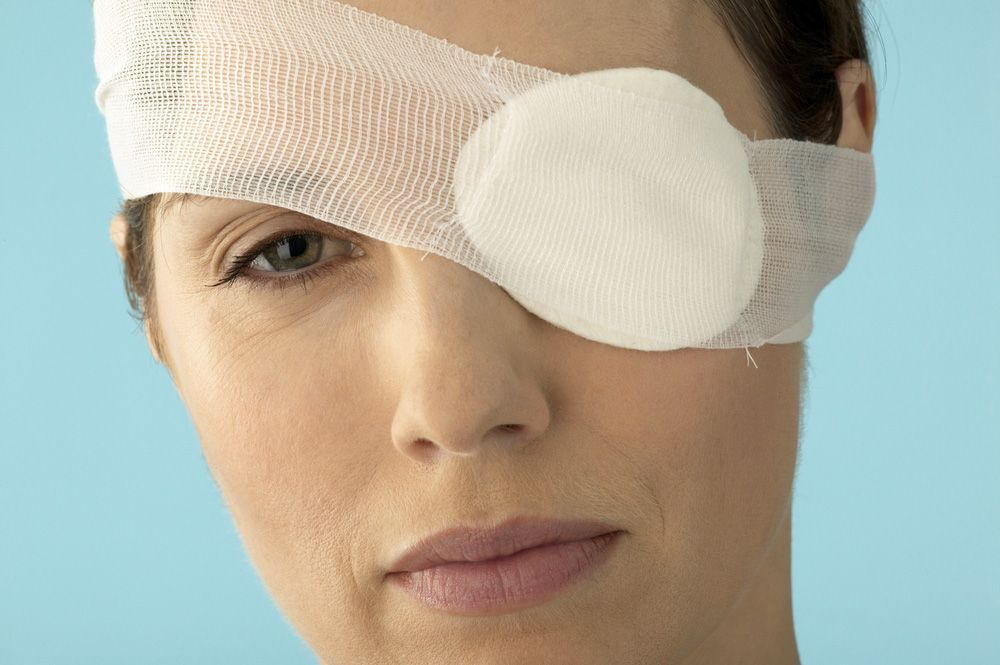 A woman wears a bandage over her left eye due to trauma