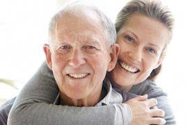 A woman hugging an elderly man from behind