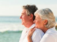 An older man and woman are looking out to the ocean and smiling.