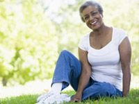 A mature lady is sitting down on the grass and smiling.