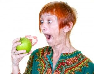 Benefits of dental implants: a woman looks on in shock at her dentures stuck in an apple