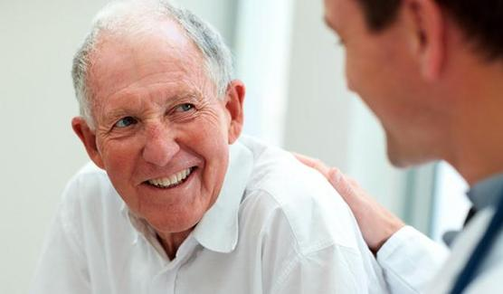 Benefits of dental implants: an older man smiles at his dentist