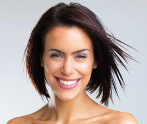 Teeth Whitening: a woman smiling directly at the camera