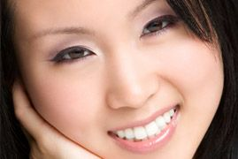 Pretty Asian woman with heavy makeup, cradling chin in hand