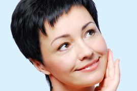 Pretty middle-aged woman with dark pixie cut looking to the side and rubbing cheek