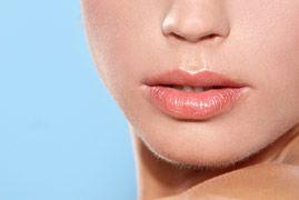 Close up of beautiful woman's plump lips with lip gloss