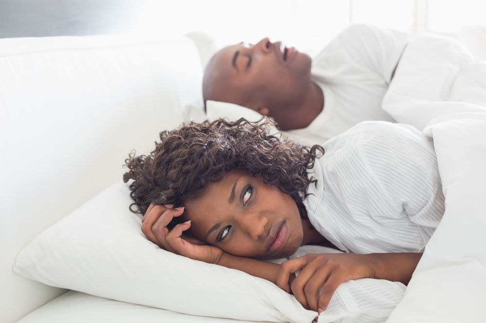 Woman in bed with a snoring man