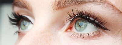 Close up of woman's green eyes with long eyelashes