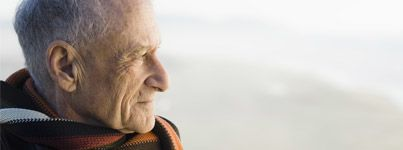 Elderly man in scarf stares wistfully over beach