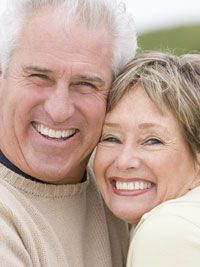 A happy elderly couple with white smiles.