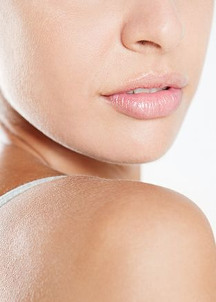 Close view of the lower half of a woman's face, chin resting on her bare shoulder