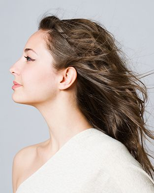 View of a woman's side profile and neck as she looks off camera