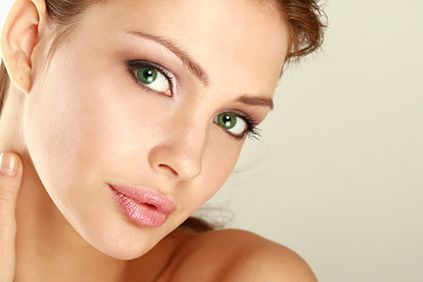 Young woman with smooth skin and green eyes looking at the camera