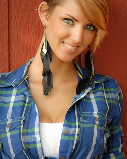A young woman smiles at camera with feather earrings, wearing a flannel shirt with open cleavage