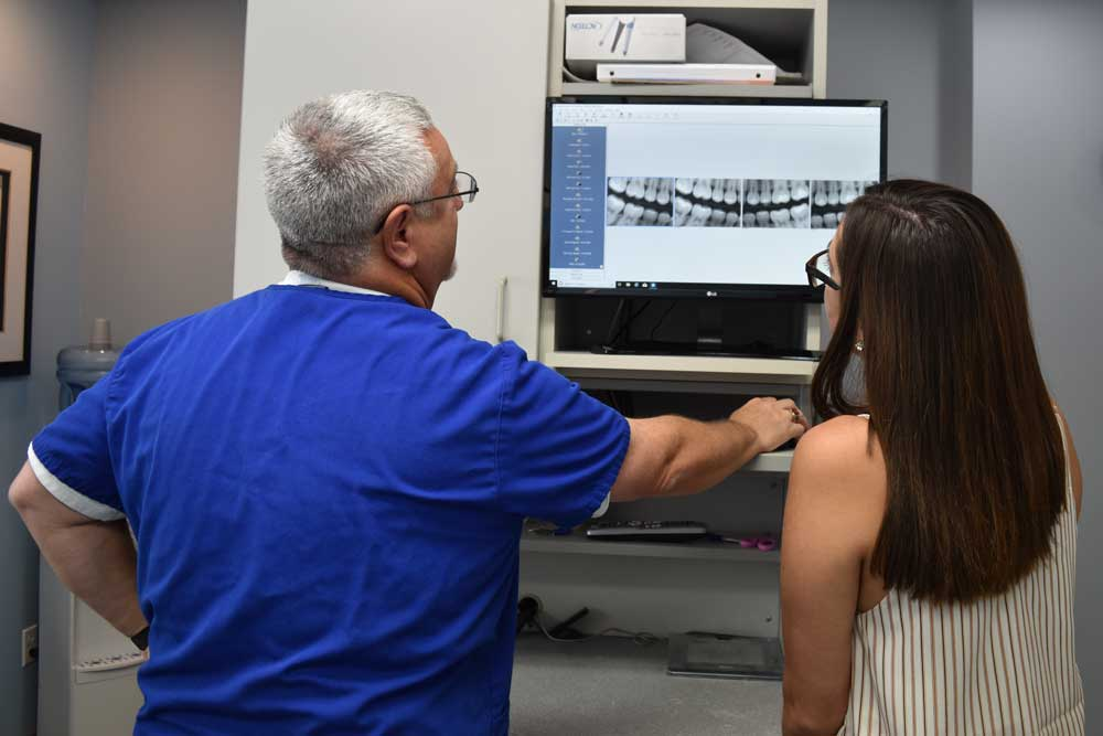 Dr. Lande showing a woman x-rays on a computer screen