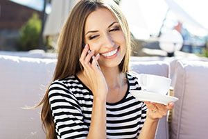Brunette woman on the telephone smiling holding a coffee cup.