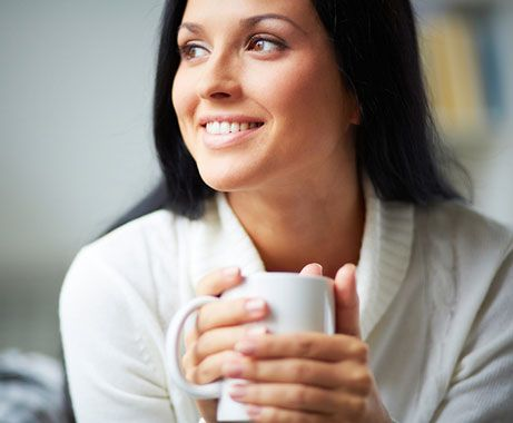 Calm, smiling woman with coffee cup.