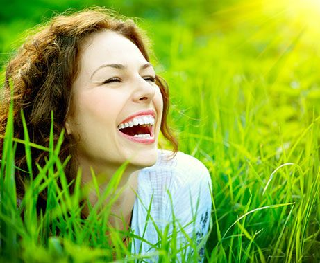 Woman smiling in the grass and sunlight outdoors.