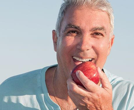 Man with white teeth about to bite apple.