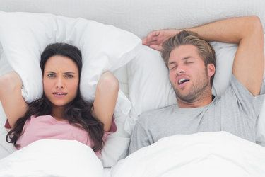 Woman stuffing pillow over her ears to muffle husband's sleep apnea snoring.