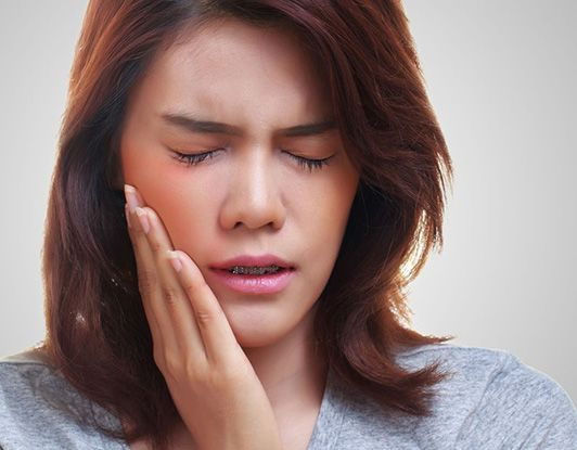 Brunette woman holding jaw in pain