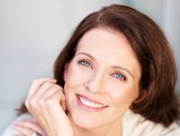 Smiling woman with auburn hair and bright blue eyes