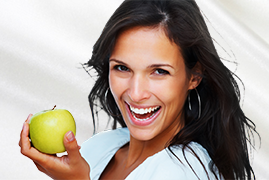 Photo of woman smiling while holding an apple