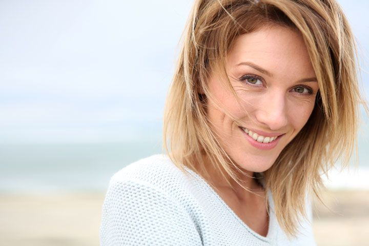 Brown-haired woman in makeup smiling seductively