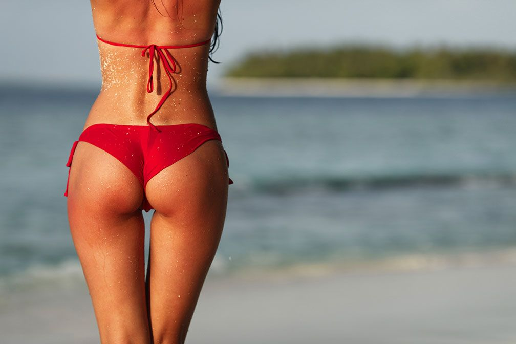Woman in red bikini on beach after sculptra butt lift